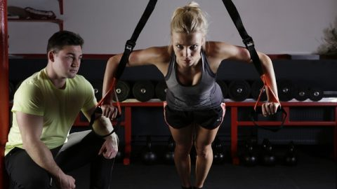 A girl doing exercise with her fitness trainer